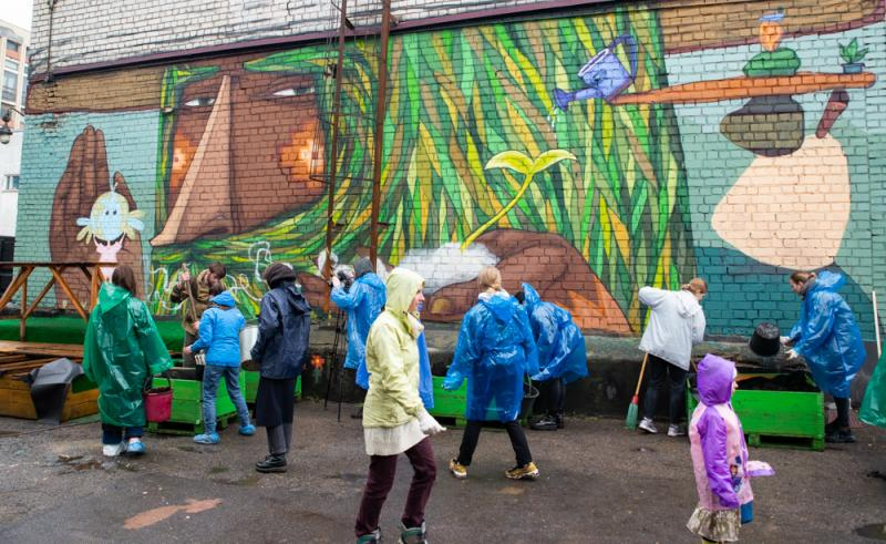 Несмотря на дождь, волонтеры помогают собирать конструкцию Городского огорода