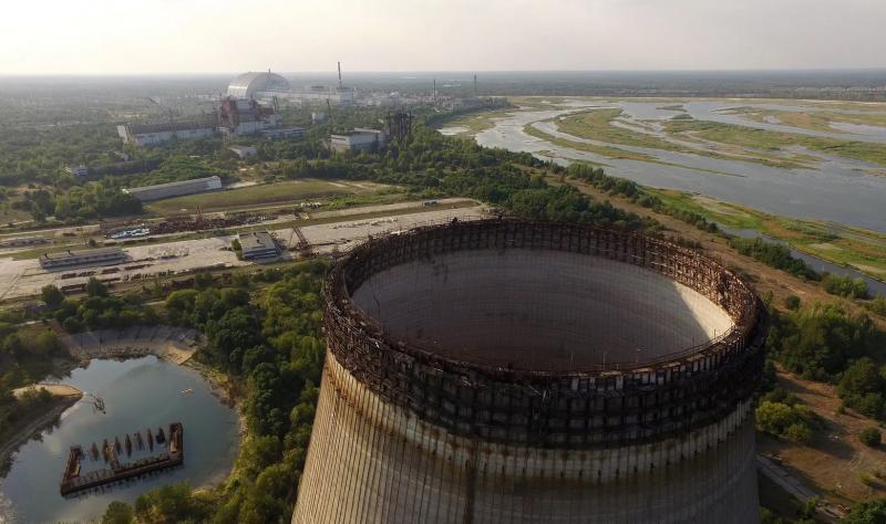Частично построенная и заброшенная градирня в Чернобыле в качестве защитного ограждения в дали возвышается над повреждённым реактором номер четыре© Шон Гэллап