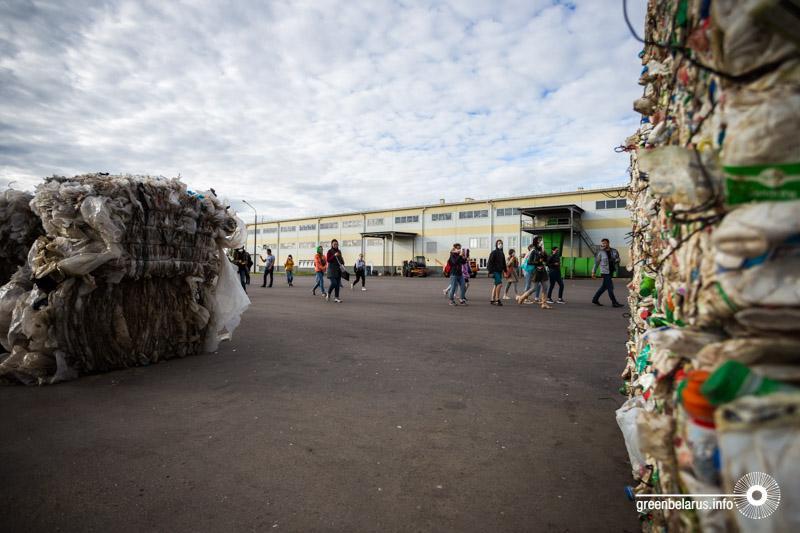 Гости идут к подиуму, по бокам – тюки отсортированных и спрессованных плёнки и пластика